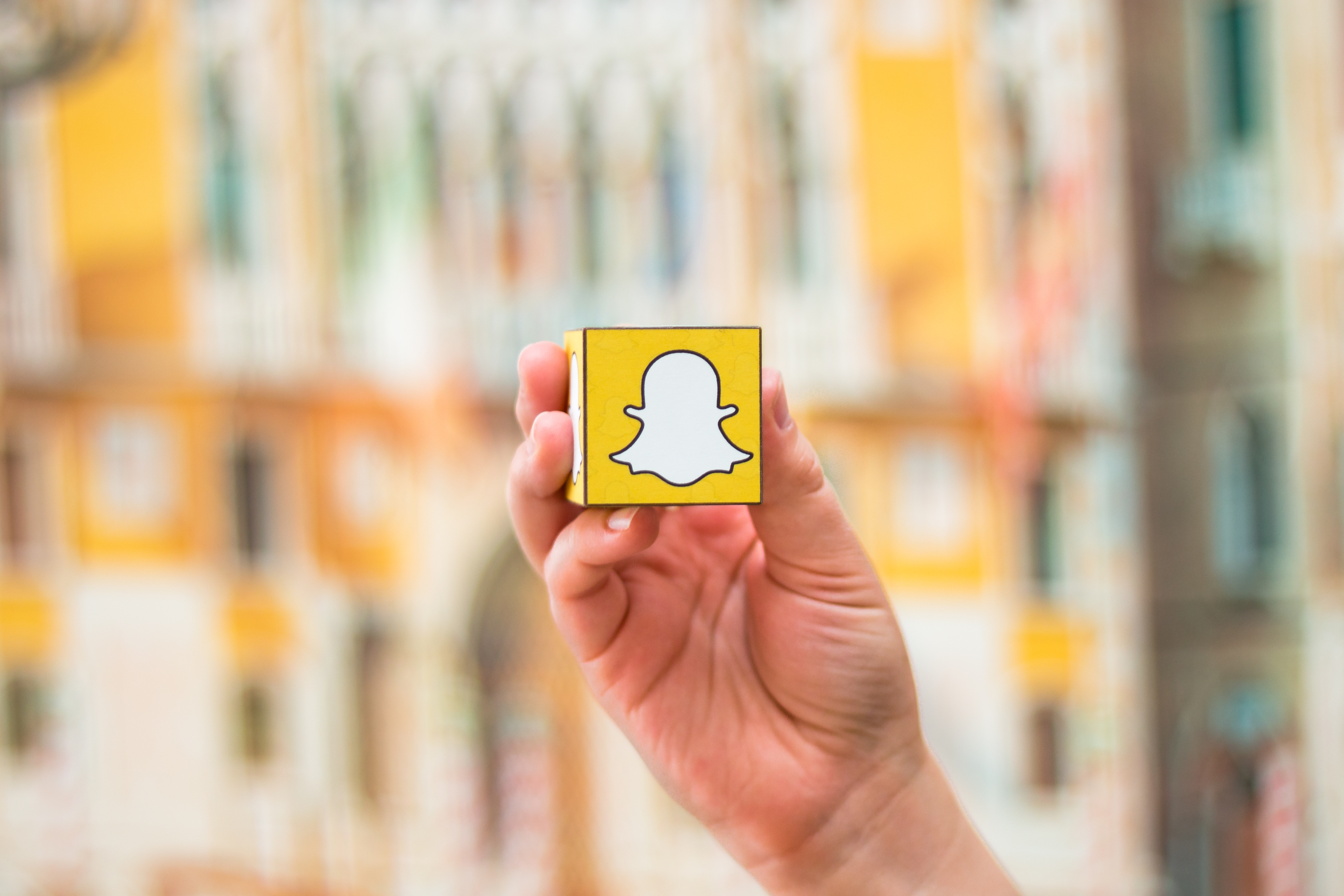 Hand holdling cube with Snapchat logo in front of blurred background.