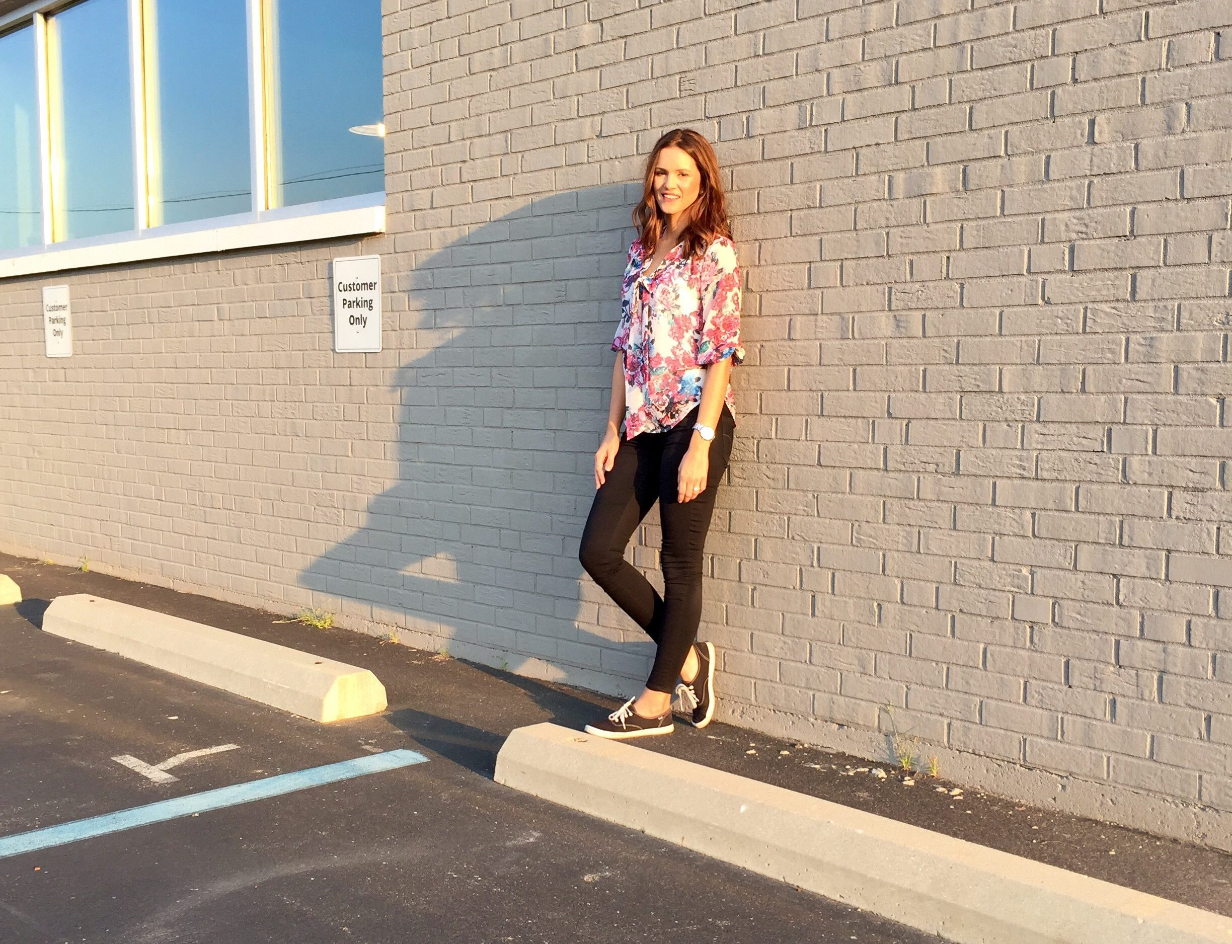 Kati Blair standing in front of gray exterior brick wall at Burkhart Marketing
