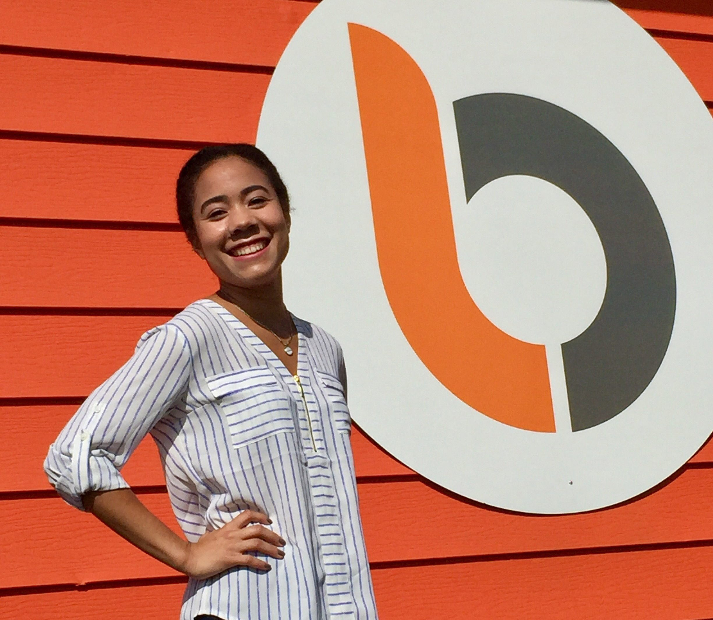 Bridget standing in front of orange wall with Burkhart Marketing logo on it