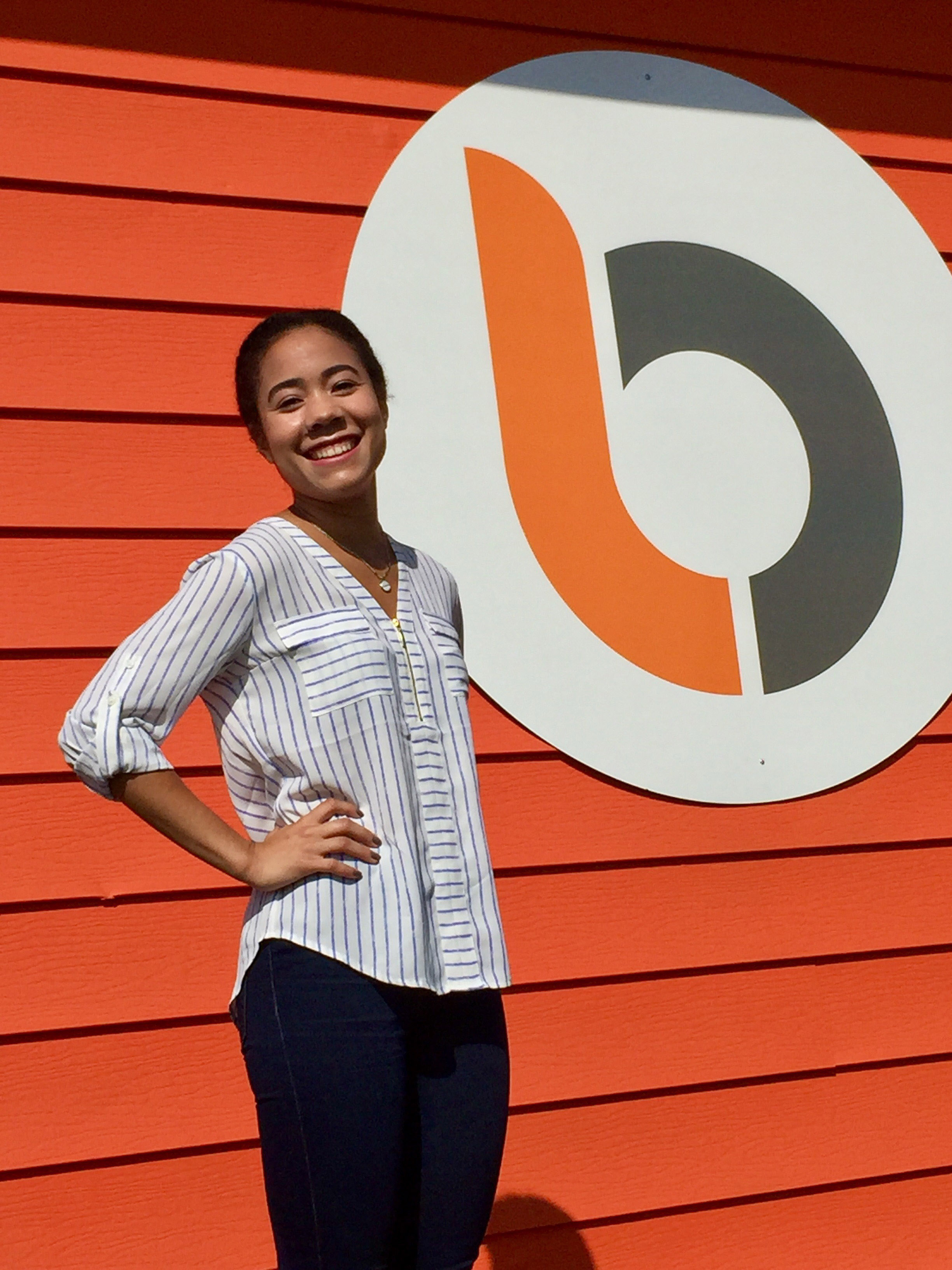 Intern standing in front of orange wall with Burkhart Marketing logo on it