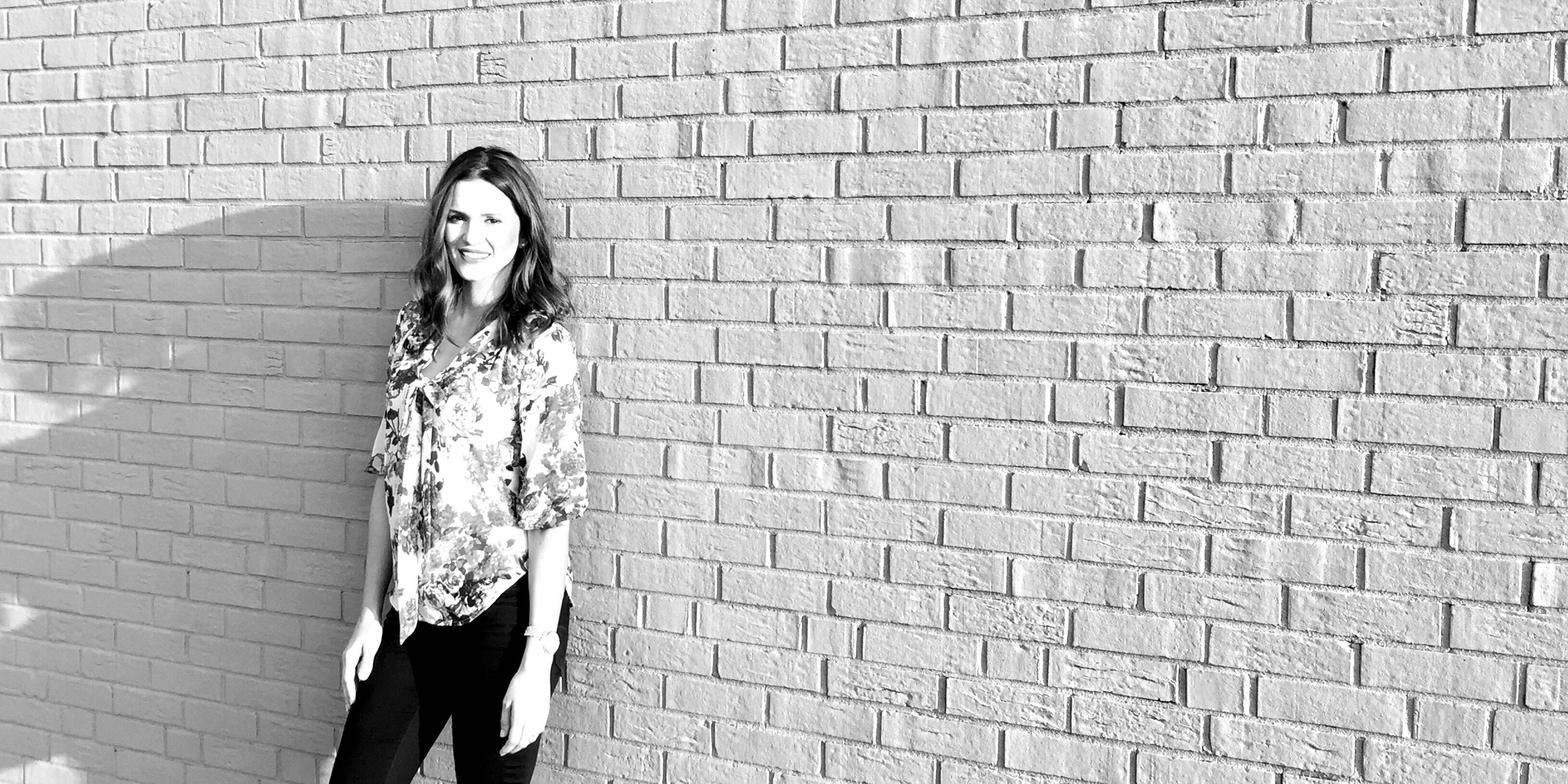 d061729a3b0d Burkhart Marketing Kati Blair standing in front of gray brick wall