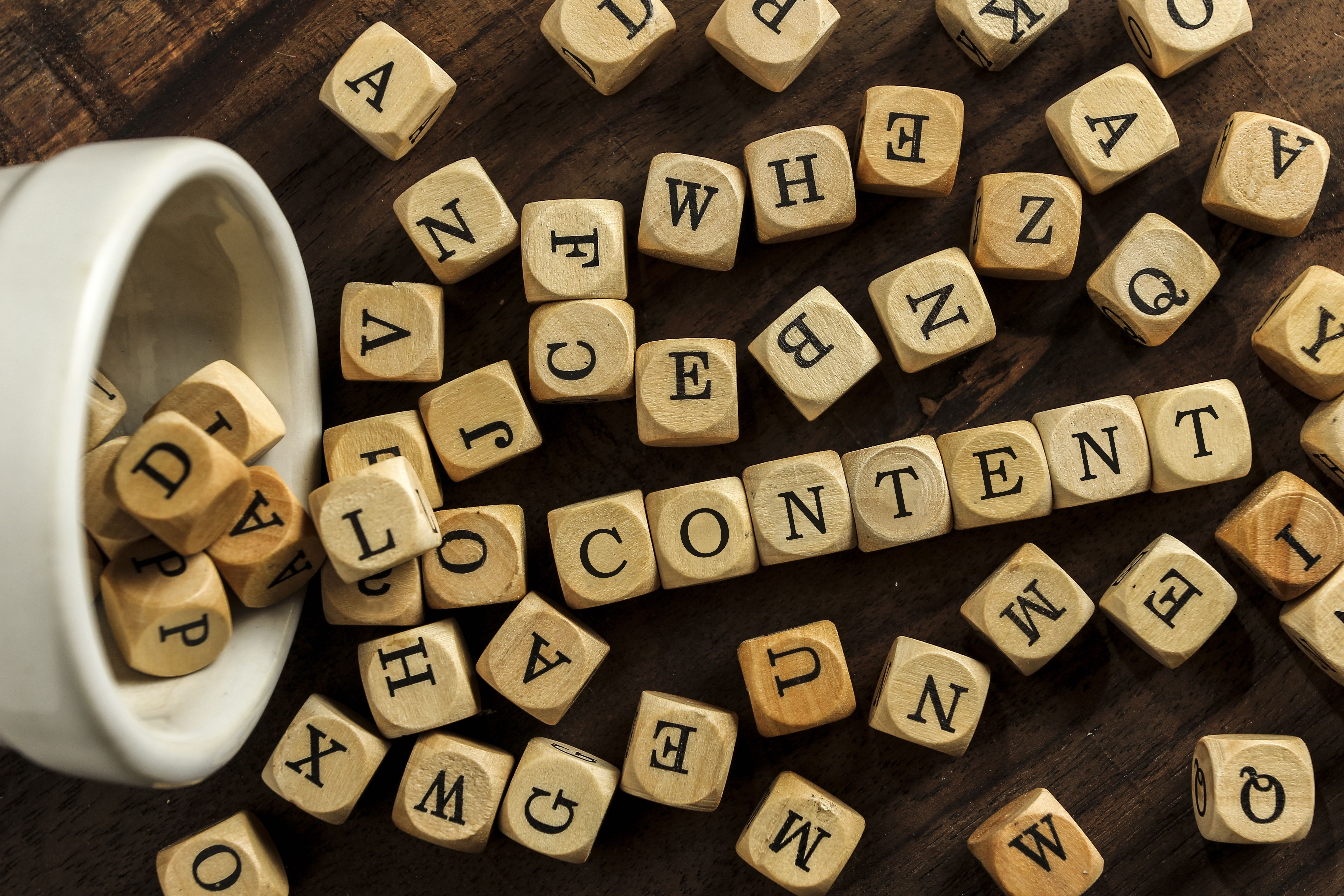 """Lettered cubes spilling out of cup and spell """"Content""""."""